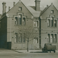 Image: A 1930 era car is parked in front of a plain two storey brick building with gable roofs.