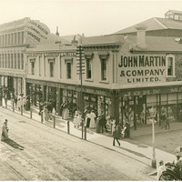 Image: a city department store, mostly two storeys but with one three storey section. Men and women in early 20th century clothes are peering in the plate glass windows at the displays.