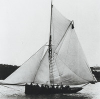 Image: A small, single-masted sailing vessel with a cutter rig coasts off a nearby shoreline. A crew of approximately a dozen men are visible standing along the vessel's length