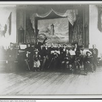 Image: Photograph of members of the German Club Band with their instruments. The picture behind on stage depicting a German rural scene.