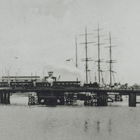 Image: A steam train crosses a bridge that extends across a narrow river. A large nineteenth century sailing vessel is visible behind the bridge, while a small rowboat operated by two men is present in the foreground