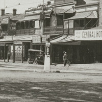 Image: An intersection of two streets in an urban area. A plinth with the words 'Keep Left' stands in the centre of the intersection. Early twentieth century cars and a horse and cart are parked in the background