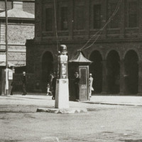 Image: An intersection of two streets in an urban area. A plinth with the words 'Keep Left' stands in the centre of the intersection. Two early twentieth century cars are parked in the background