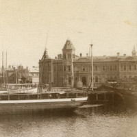 Image: A nineteenth-century steamship with twin funnels and two masts moored at a wharf on the waterfront of a port town. A handful of large nineteenth-century warehouses and other buildings are visible along the waterfront