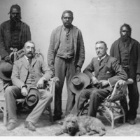 Image: R.T. Maurice's expedition party. Three Aboriginal men standing, two white men sitting, one dog on the floor. All the men wear suits.