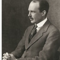 Image: side view of man in suit, seated