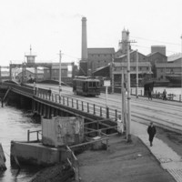 Image: A tram and four pedestrians cross a bridge across a river in a port. A complex of nineteenth-century buildings and a wooden-hulled hulk are visible in the background