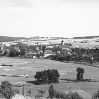 Image: A panoramic view of a German town. There are many houses. A number of large, open fields surround the town