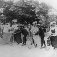 Image: three women on bicycles about to begin a race. Men hold the bicycles steady.
