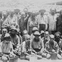 Image: A large group of Aboriginal men, two at the front have tin cans possibly from ration distribution