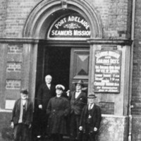 Image: A group of men in early twentieth century attire stand in front of a large, nineteenth century two-storey bluestone building. Signs in the first floor windows read 'Seamen's Mission & Sailors' Rest'