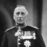Image: A photographic portrait of a middle-aged Caucasian man wearing full military dress uniform including sword, plumed helmet and spurs. On his chest he wears an array of medals and orders