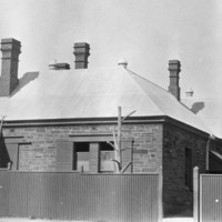 Image: Black and white photograph of the outside of a 19th century villa style building