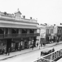 Image: Shops and pedestrians seen from an elevated position on the opposite side of the road. The row of two storey shops in the centre has parapet and a cantilever verandah. The building on the left is covered in scaffolding.
