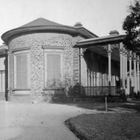 Image: A single storey bluestone building with rounded wall, arched portico and verandah