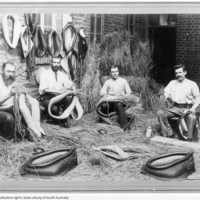 Image: group of men holding and making leather horse collars