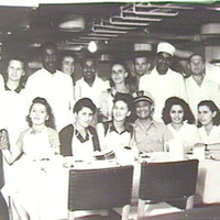 Image: Nineteen men and women in a ship's kitchen. Seven women and one man are seated at a table, the rest stand behind them. They are all wearing white or aprons
