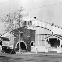 Image: a single storey wooden building with a pitched gable roof and protruding arched brick entrance way. There are 1920s era cars parked outside.