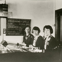 "Image: Three women are seated at a switchboard. Behind them is a sign that says ""Emergency Calls"" and lists numbers for police, fire, ambulance, hospital and waterworks"