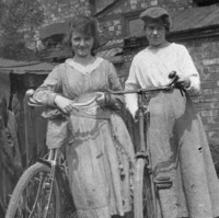 Image: two girls standing outside with their new bicycles