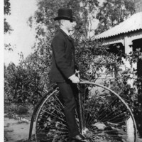 Image: man in a top hat and suit seated on a penny-farthing bicycle