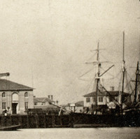 Image: A mid-nineteenth century landscape photograph of a port waterfront. Several buildings are visible next to the water, and a small number of sailing ships are moored alongside a large wharf