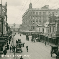 Image: City buildings and sparse horse-drawn traffic in Rundle Street, taken from an elevated position. Dominating the image is a huge five storey hotel building with a cupola on the corner of its roof.