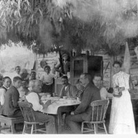 Image: Men and Women around a table underneath a brush and eucalyptus shelter