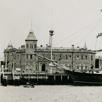 Image: A large, three-masted sailing ship is moored alongside a wharf in a port town. Several buildings, including a large nineteenth-century structure with an octagonal tower in one corner, are visible in the immediate background