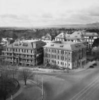 Image: A collection of large, three and four storey buildings clustered together on the corner of two main roads