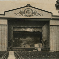 Image: a large open air theatre with rows of seats facing a stage with an outdoor scene as its backdrop