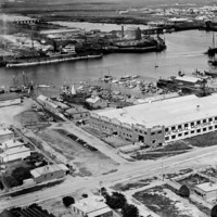 Image: An aerial photograph of a port town, at the centre of which is a large building with the words 'General Motors Aust. Pty. Ltd' emblazoned across it. Sailing and motor vessels of various types are visible in the river beyond the building