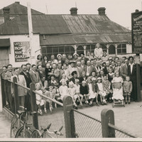 Image: A large group (over fifty) of people pose outside a hall for a group photo. The first two rows are children.