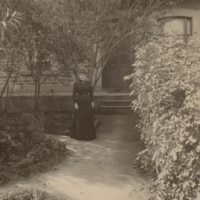 Image: Black and white photograph of a woman in front of a house