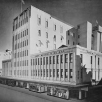 Image: a large 1930s era department store building with displays in its ground floor windows. The majority of the building is three storeys high, however, a seven storey tower protrudes from its centre.