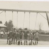 Image: A group of children pose for a photograph under a swing in a park. A building and trees are visible in the background