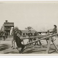Image: A group of children play on see-saws in a park. A street and row of buildings are visible in the background