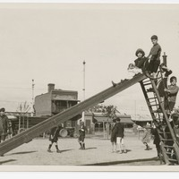 Image: A small group of children play on a slide in a park. A street and row of buildings are visible in the background