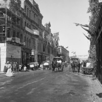 Image: A wide dirt road with a number of pedestrians and horse drawn vehicles. The buildings are decorated with flags and greenery. One of the buildings on the left is still under construction and is covered in scaffolding.