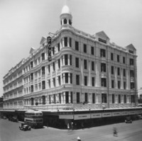 Image: a large five storey building with a verandah situated on a street corner. The corner of the building is rounded and extends into a cupola with a flagpole. A double decker bus passes on the street outside while a policeman stands directing traffic.
