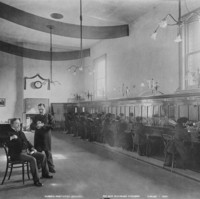Image: Interior view of a telephone exchange. A row of women switchboard operators are supervised by a well dressed woman sitting at a raised desk on the left.