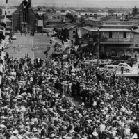 Image: A large group of people dressed in 1940s attire gather on the approach to a bridge. Several buildings are visible just beyond the bridge approach