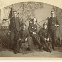 Image: a studio group of five members of the South Australia Bicycle Club with penny farthing bicycles; they are wearing the club uniform with helmet hats, one carries a small bugle on a shoulder belt.