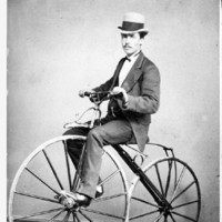 Image: man in a top hat and suit riding a velocipede with wooden wheels