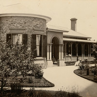 Image: a small number of women and girls in 1860s era clothing stand outside a single storey bluestone house with curved wall, columned portico and verandah.