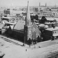 Image: a high angle view of a low lying city. In the foreground, situated at a crossroad, is a stone church with a single square tower with crenellations, which becomes octagonal with a very steeply pitched roof, to one side  of the building