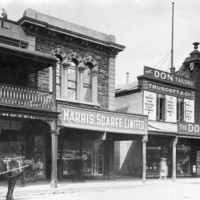 Image: a row of two storey shops with verandahs line a dirt road. To the right a horse drawn cart stands outside a hotel with a balcony.