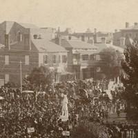 Image: crowds surrounding stone statue of standing man