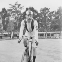 Image: cyclist wearing a cap and the number five on his forearm prepares for a race