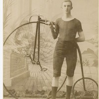 Image: young cyclist holding onto the handlebar of his penny-farthing bicycle